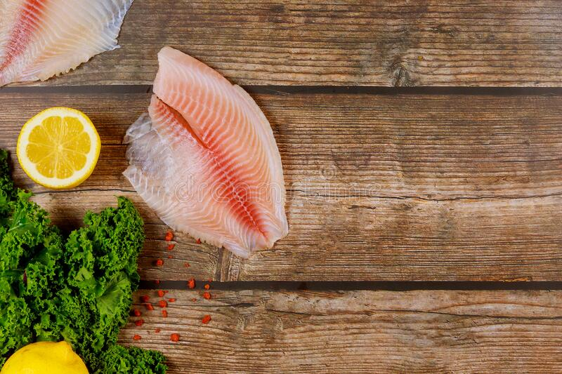 Pink tilapia with lemon and spices on wooden background royalty free stock photography