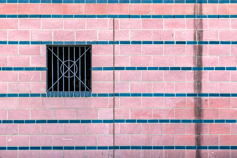 Pink tiled wall with dirty water stains and a metal barred window royalty free stock photography