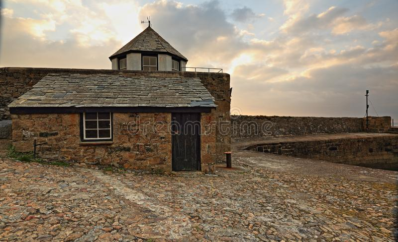 Harbour masters hut at Charlestown, Cornwall. Pink tinted clouds sit behind the harbour masters hut which sits on the quayside at Charlestown in Cornwall royalty free stock image