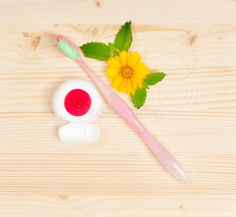 Pink toothbrush. Toothbrush with toothpaste and tooth thread over wooden surface royalty free stock photo