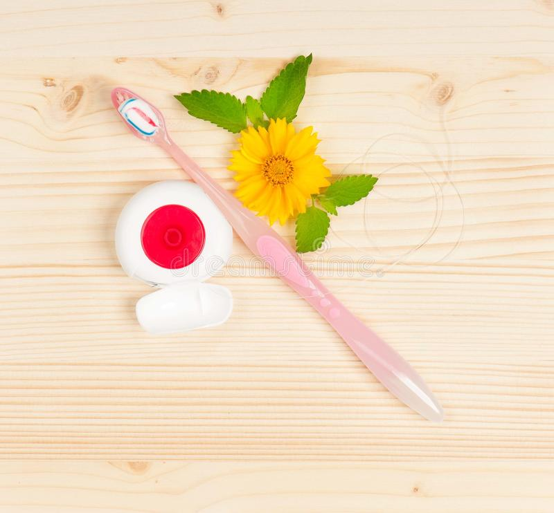Pink toothbrush. Toothbrush with toothpaste and tooth thread over wooden surface royalty free stock photography