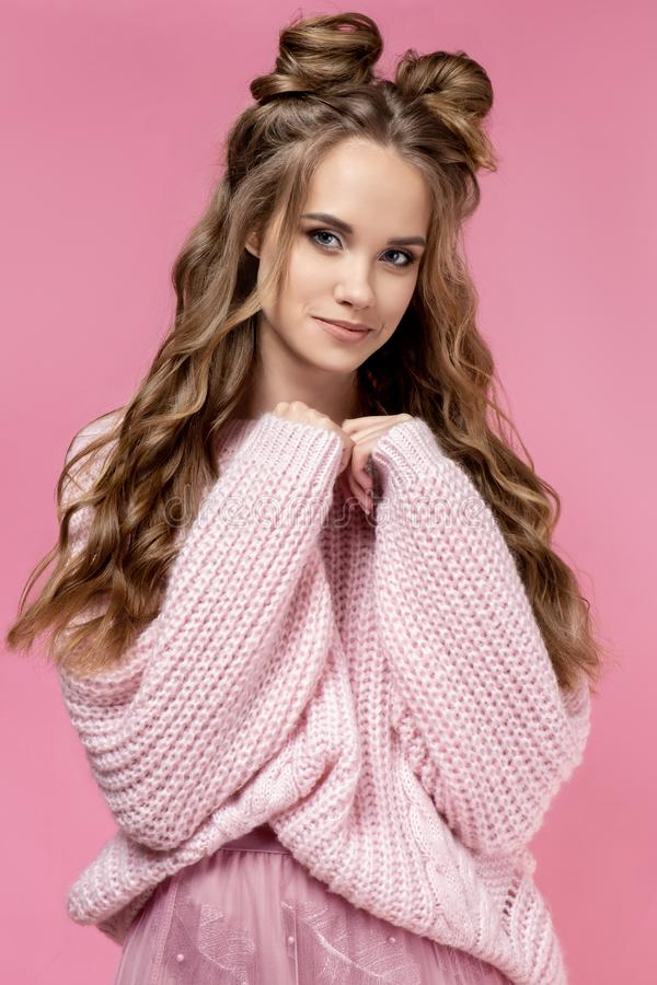 Pretty young girl in a pink sweater on a pink background with a haircut and curly long hair. royalty free stock photos