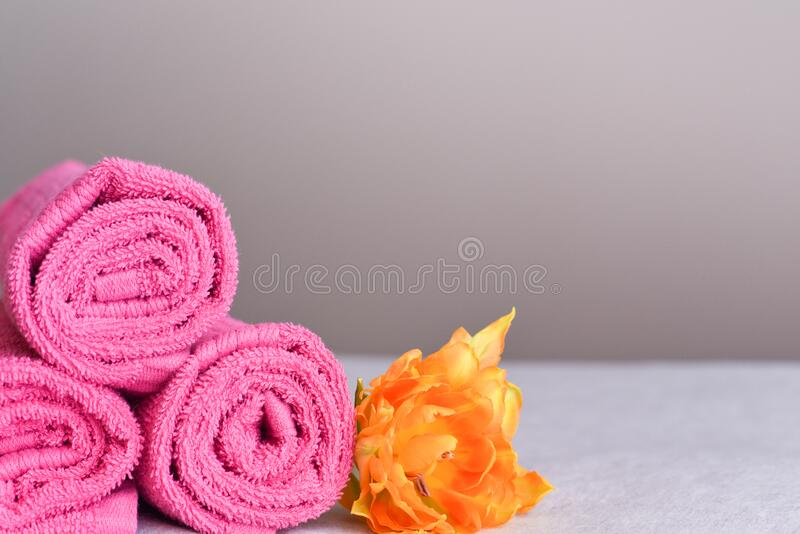 Pink towels in rolls with a yellow flower. A stack of new clean pink towels in rolls with a yellow flower, the concept of freshness and cleanliness royalty free stock photo