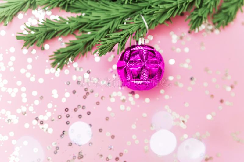 Pink toy on the branches of a Christmas tree on the pink background with glitters and bokeh flat lay. Christmas post card royalty free stock photos