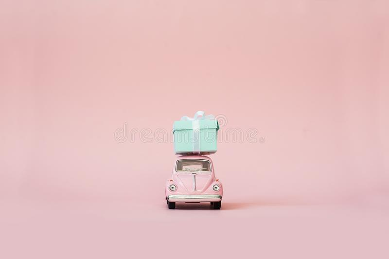 Pink toy retro model car delivering gift box for Valentine`s day on pink background. Volkswagen Beetle on pink background. stock images