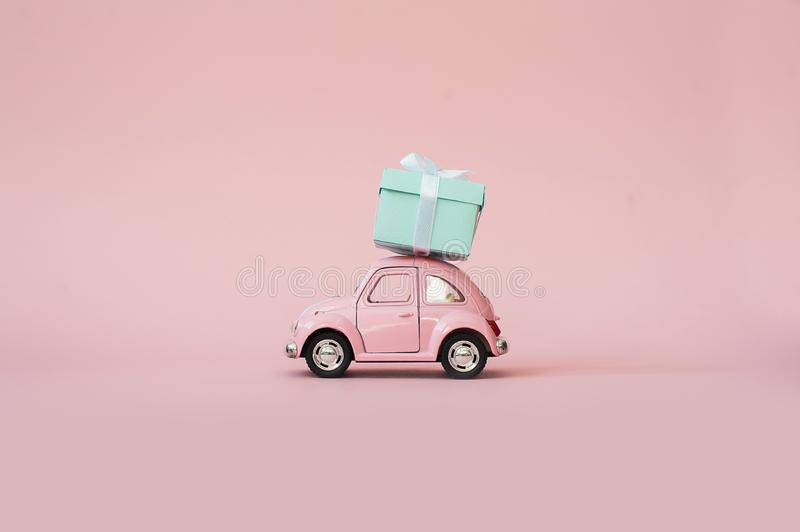 Pink toy retro model car delivering gift box for Valentine`s day on pink background. Volkswagen Beetle on pink background. royalty free stock image