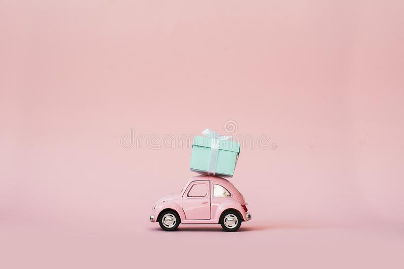Pink toy retro model car delivering gift box for Valentine`s day on pink background. Volkswagen Beetle on pink background. Delivery concept stock images