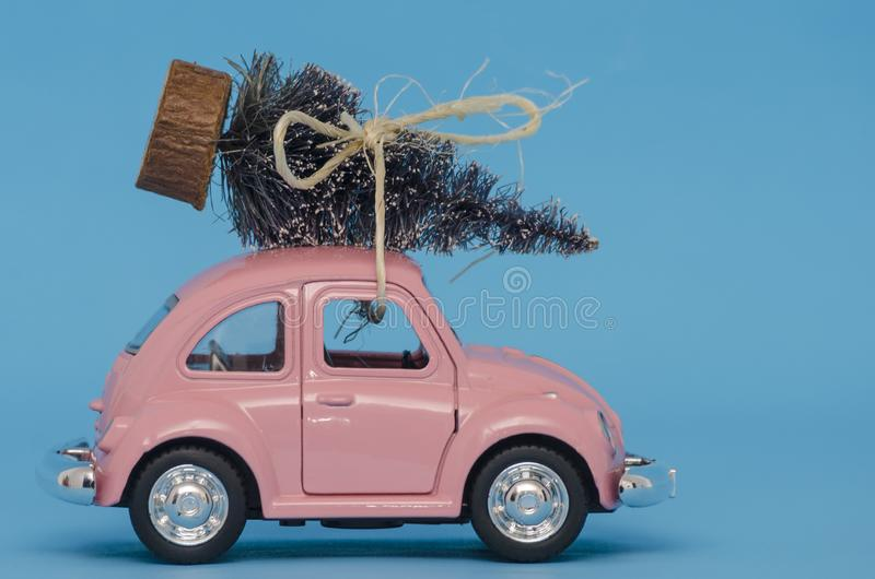 Pink toy Volkswagen Super Beetle car with Christmas tree royalty free stock photography
