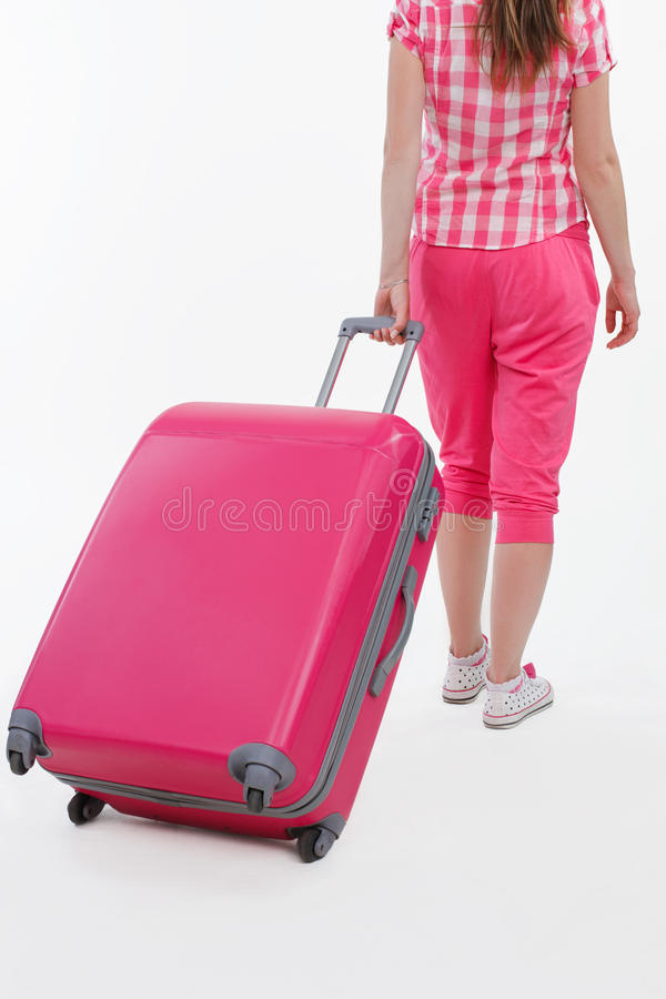 Pink travel bag and traveller girl holding it. stock images