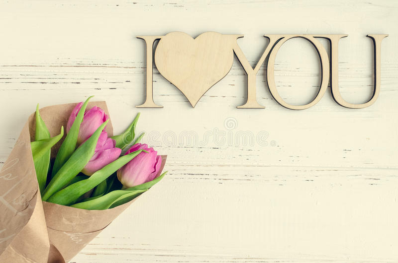 Pink tulip flowers with wooden words I LOVE YOU royalty free stock image