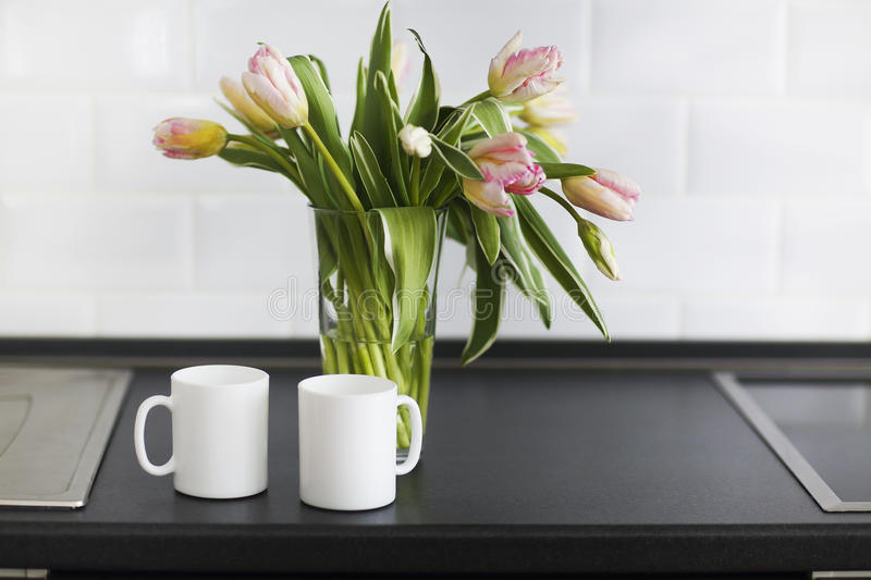 Pink tulips bouquet in glass vase on the kitchen. Still life with pink tulips bouquet in glass vase on the kitchen royalty free stock photos