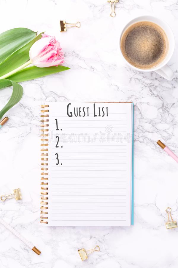 Pink tulips with festive stationary and coffee on white marble background. Guest List wording. Copy space. Top view. Vertical royalty free stock photos
