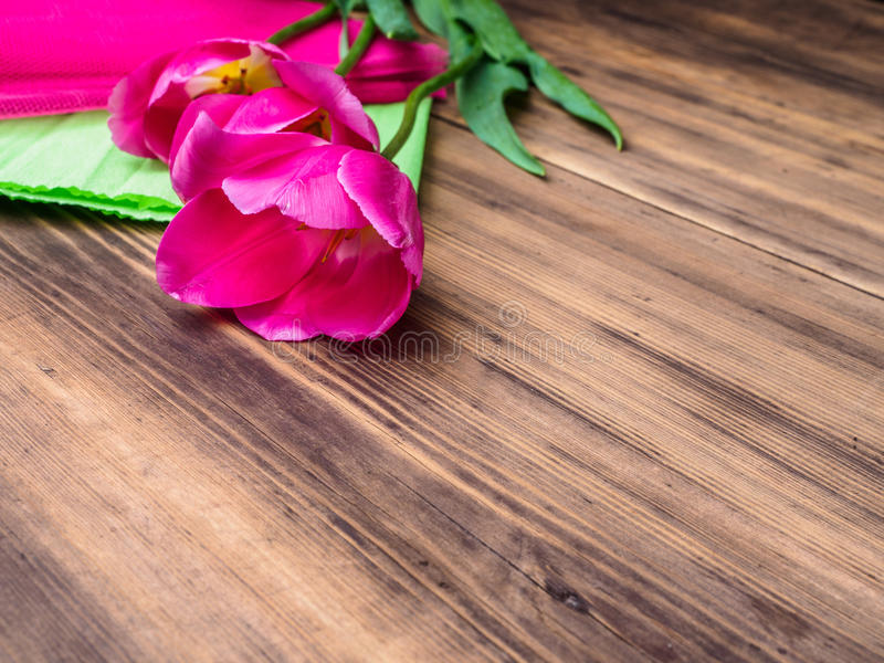 Pink tulips, floral arrangement on wooden background with green paper and space for message. Background for Mother`s Day stock photo