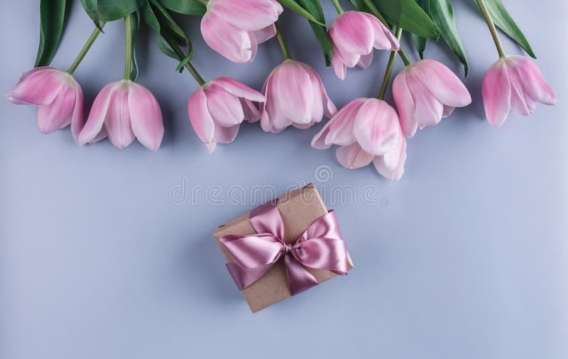 Pink tulips flowers and gift over light blue background. Greeting card or wedding invitation. Flat lay, top view, copy space royalty free stock images