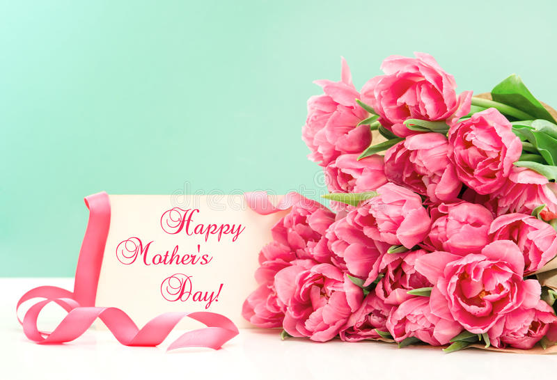 Pink tulips and greeting card. Happy Mothers Day. Pink tulips and greeting card with sample text Happy Mothers Day stock images