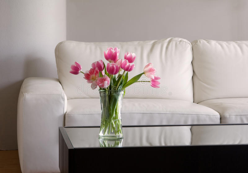 Pink tulips in modern living room stock image