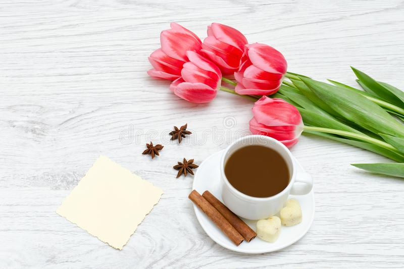 Pink tulips, mug of coffee and cinamon. Empty postcard. Llight w. Ooden background royalty free stock photo