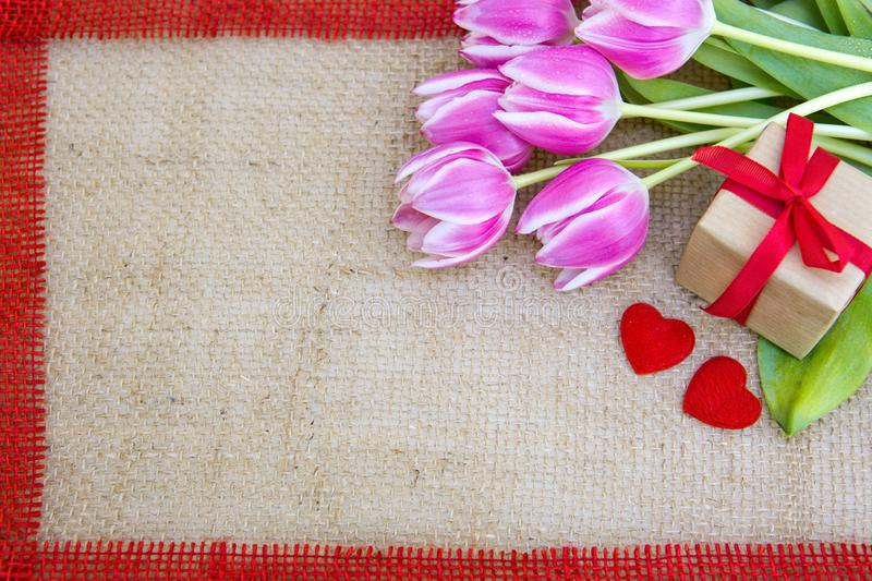 Tulips and two red hearts on brown cloth Background. royalty free stock image