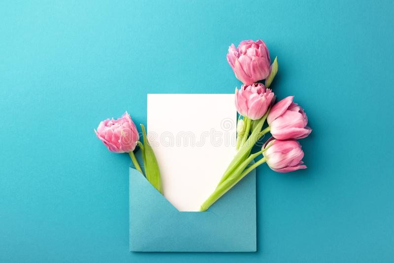 Pink tulips and white card in envelope. royalty free stock image