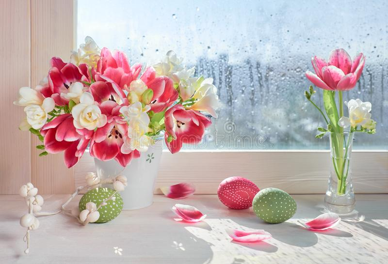 Pink tulips and white freesia flowers with Easter decorations on royalty free stock images