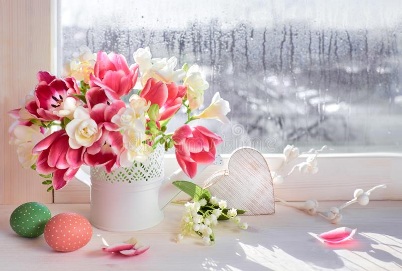 Pink tulips and white freesia flowers with Easter decorations on stock photo