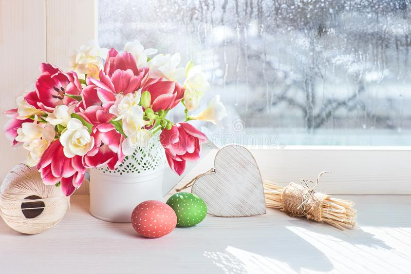 Pink tulips and white freesia flowers on the window board, Easter decorations royalty free stock image