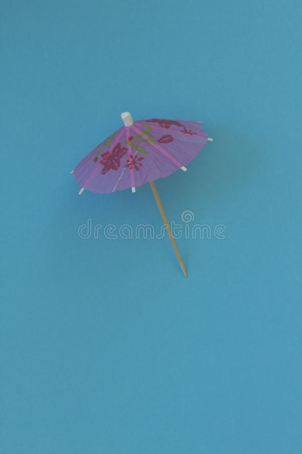 Pink umbrella for cocktail on a blue paper background. Conceptual image of summer. Minimalism. Abstraction. Creativity. royalty free stock photography