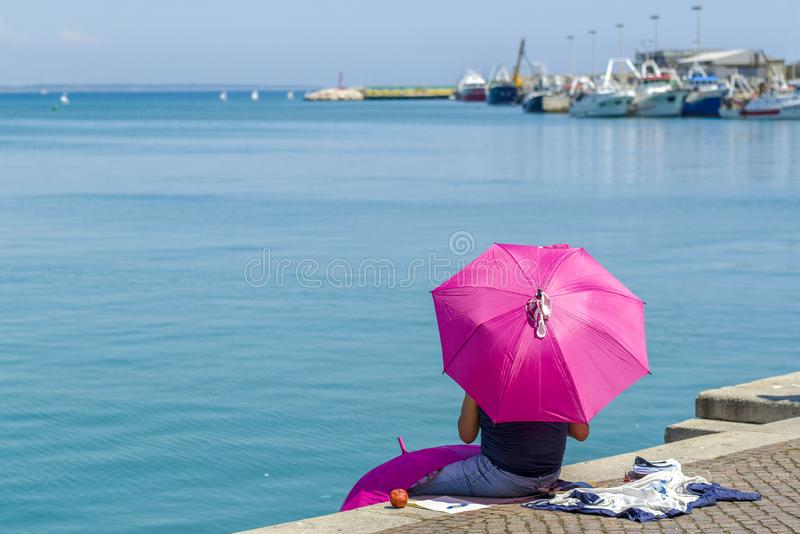 The pink umbrella. Man sits on a quay, protecting himself from the sun with a pink umbrella royalty free stock photography