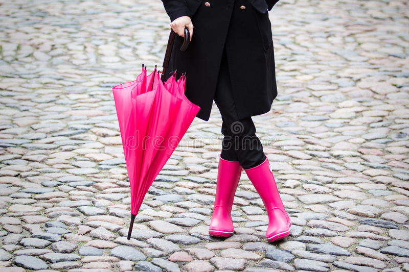 Pink umbrella and pink rubber boots. Woman with pink rubber boots holding pink umbrella royalty free stock image