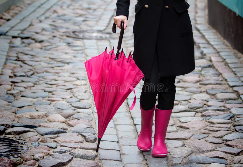 Pink umbrella and pink rubber boots. Woman with pink rubber boots walking down the street holding pink umbrella royalty free stock image