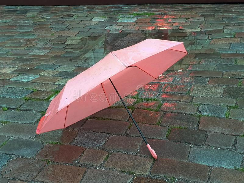 Pink Umbrella on Street cafe wet asphalt  coral  on wet rain drops evening  light   Rainy Autumn relax in Old Town empty ci. Old town Pink Umbrella on Street wet royalty free stock photos