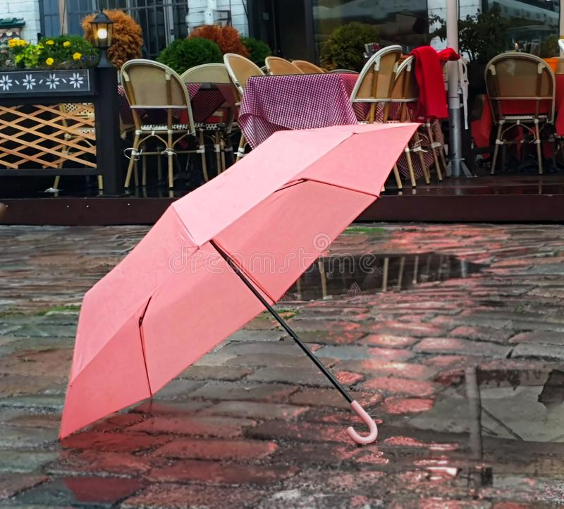 Pink Umbrella on Street cafe wet asphalt  coral  on wet rain drops evening  light   Rainy Autumn relax in Old Town empty ci. Old town Pink Umbrella on Street wet royalty free stock photography