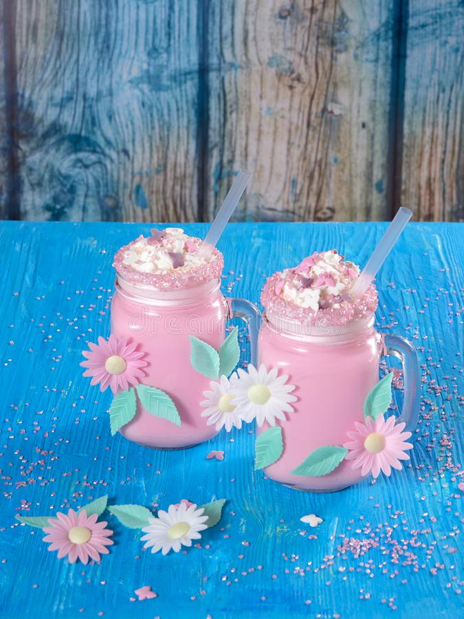 Pink unicorn milk shake with whipped cream, sugar and sprinkles. Pink unicorn milk shake with whipped cream sugar and sprinkles set on a blue wooden board with a royalty free stock photo