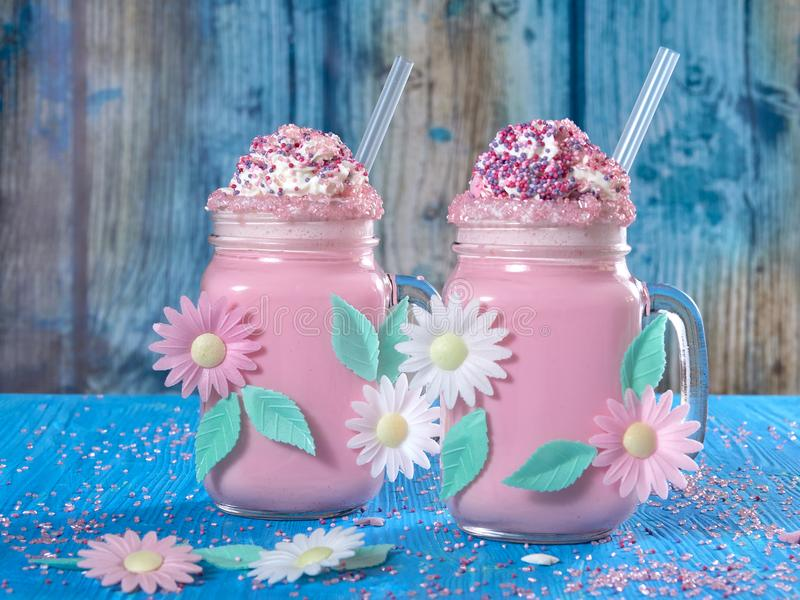 Pink unicorn milk shake with whipped cream, sugar and sprinkles. Set on a blue wooden board, with a distressed blue wood background royalty free stock photos