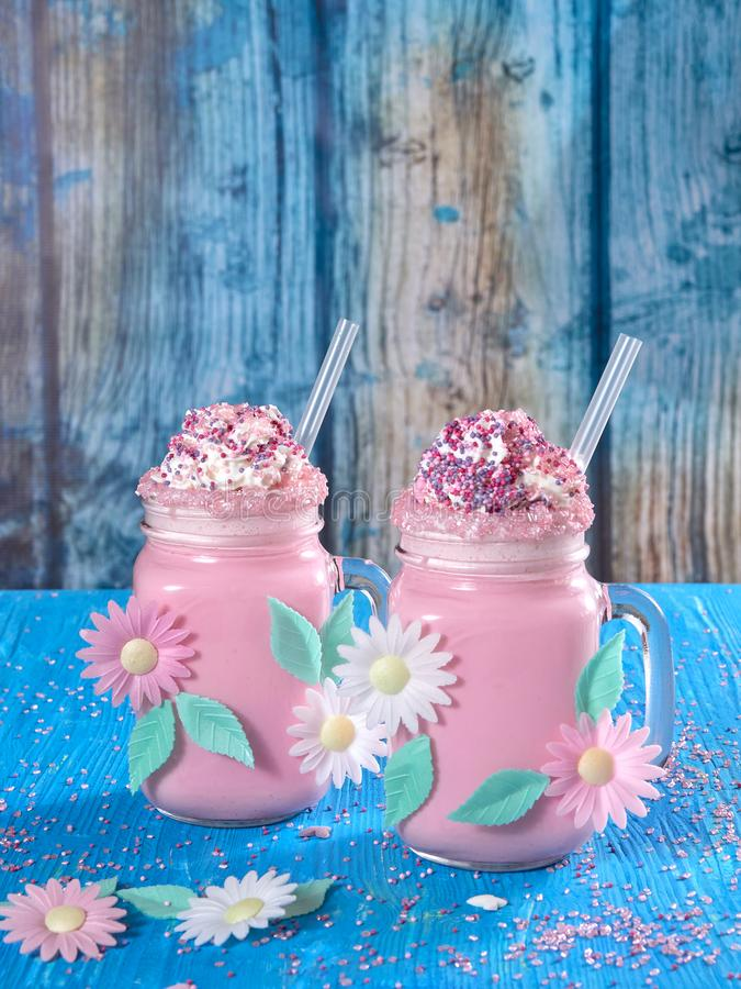 Pink unicorn milk shake with whipped cream, sugar and sprinkles. Set on a blue wooden board stock photography