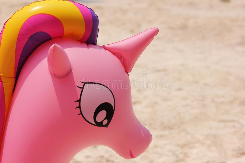 The unicorn`s head from the pink water wings closeup. Concept of summer holidays and the beach royalty free stock images