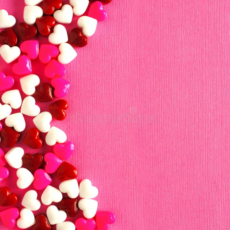 Pink Valentines Day background with candy heart border. Valentines Day candy curved border on a pink paper background stock image