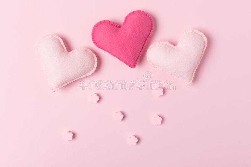 Pink Valentines day congratulation or love triangle concept with felt craft hearts. And flowers on pastel background with copy space. Tender template with hand stock images