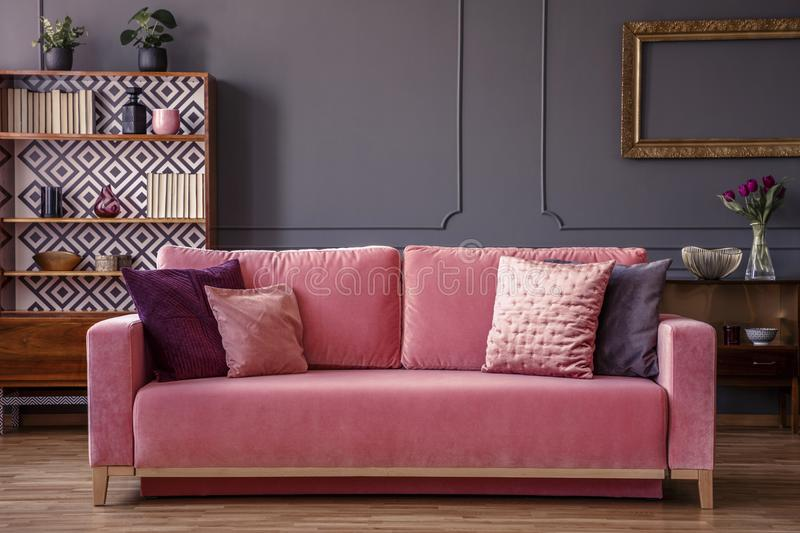 Pink velvet couch with decorative pillows standing in grey living room interior with vintage cupboard, fresh plants and molding o stock photos