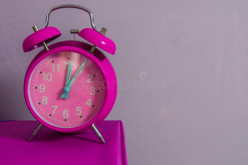 Pink vintage alarm clock standing on a table with a purple wall in the background stock images