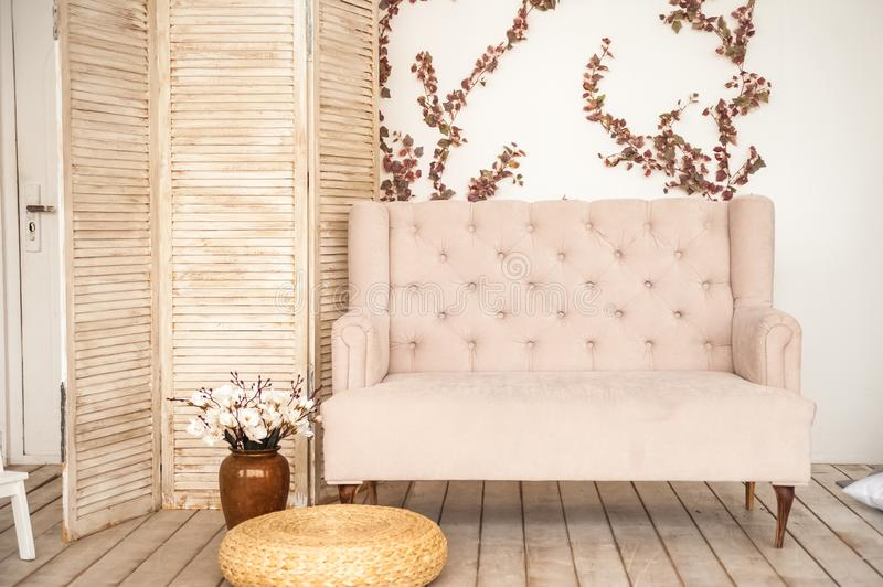 Pink vintage sofa and screen in rustic style. Interior of a bright Scandinavian living room with flowers on the wall.  stock photos