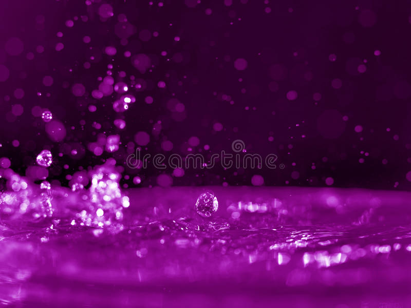 Pink water glow. Water drop with pink particle background stock photos