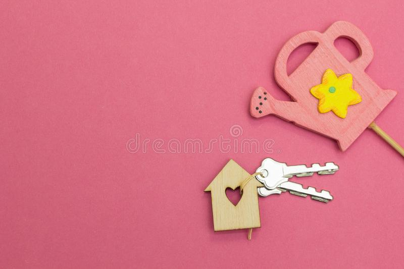 A pink watering can is watered by a wooden house on a pink background stock image