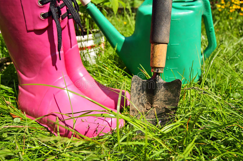Pink wellingtons in the Spring garden. Pink wellingtons and a spade in the Spring garden royalty free stock image