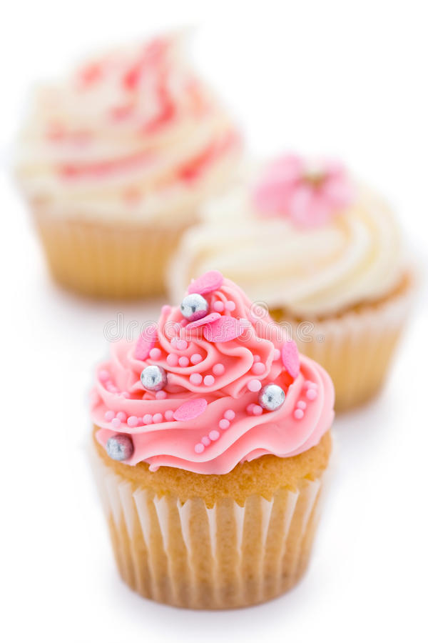 Pink and white cupcakes. Trio of pink and white cupcakes against white stock photos