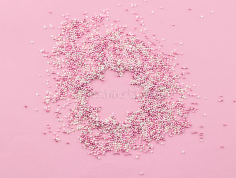 Pink and white edible pearlized sprinkles on pink background - Cake topping pearly pink with flower shape copy space in centre. Sprinkles top view photo royalty free stock photos