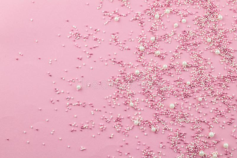 Pink and white edible pearlized sprinkles on pink background - Cake topping pearly pink sprinkles top view photo. With copy space royalty free stock photos