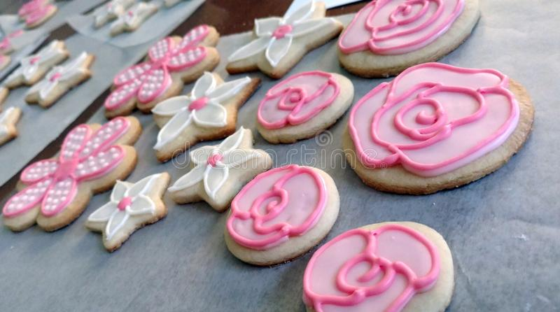 Pink and White Flower Cookies. These pink and white flower cookies have just been iced and are sitting on parchment paper waiting for the icing to set! The royalty free stock photo