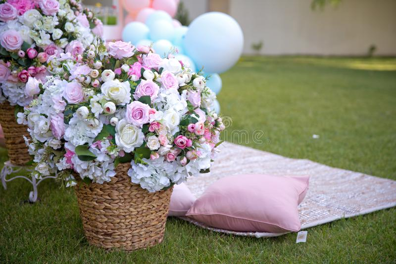 Pink and white Flowers Basket Green Grass Garden Summer . Summer Picnic on the lawn. blue balloon . Closeup of picnic basket with stock photo