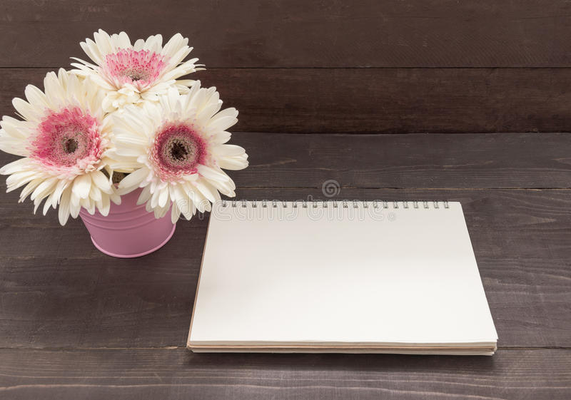 Pink and white gerbera flowers are in the flowerpot, on the wood. En background with notebook royalty free stock images